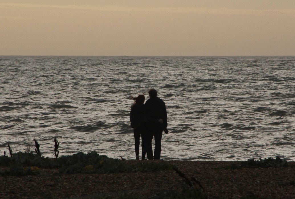 Man and woman in silhouette satnding on beach looking out to see