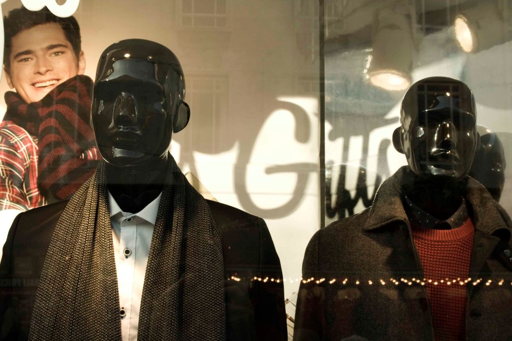 Lifeless models in window of shop- man's smiling face in background