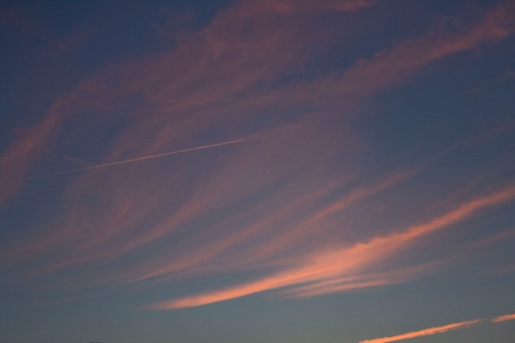 Sunset sky - purple blue and pink with the white trail of a plane