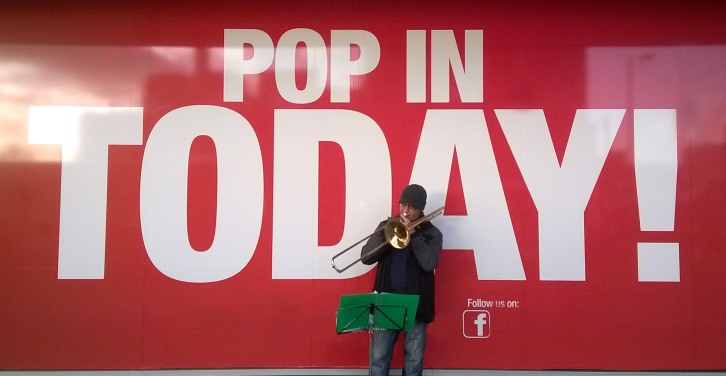 Man playing a trombone in front of store.  SIgn in window says Pop In Today